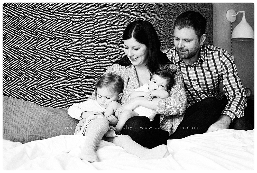 beautiful family on the bed with their newborn girl