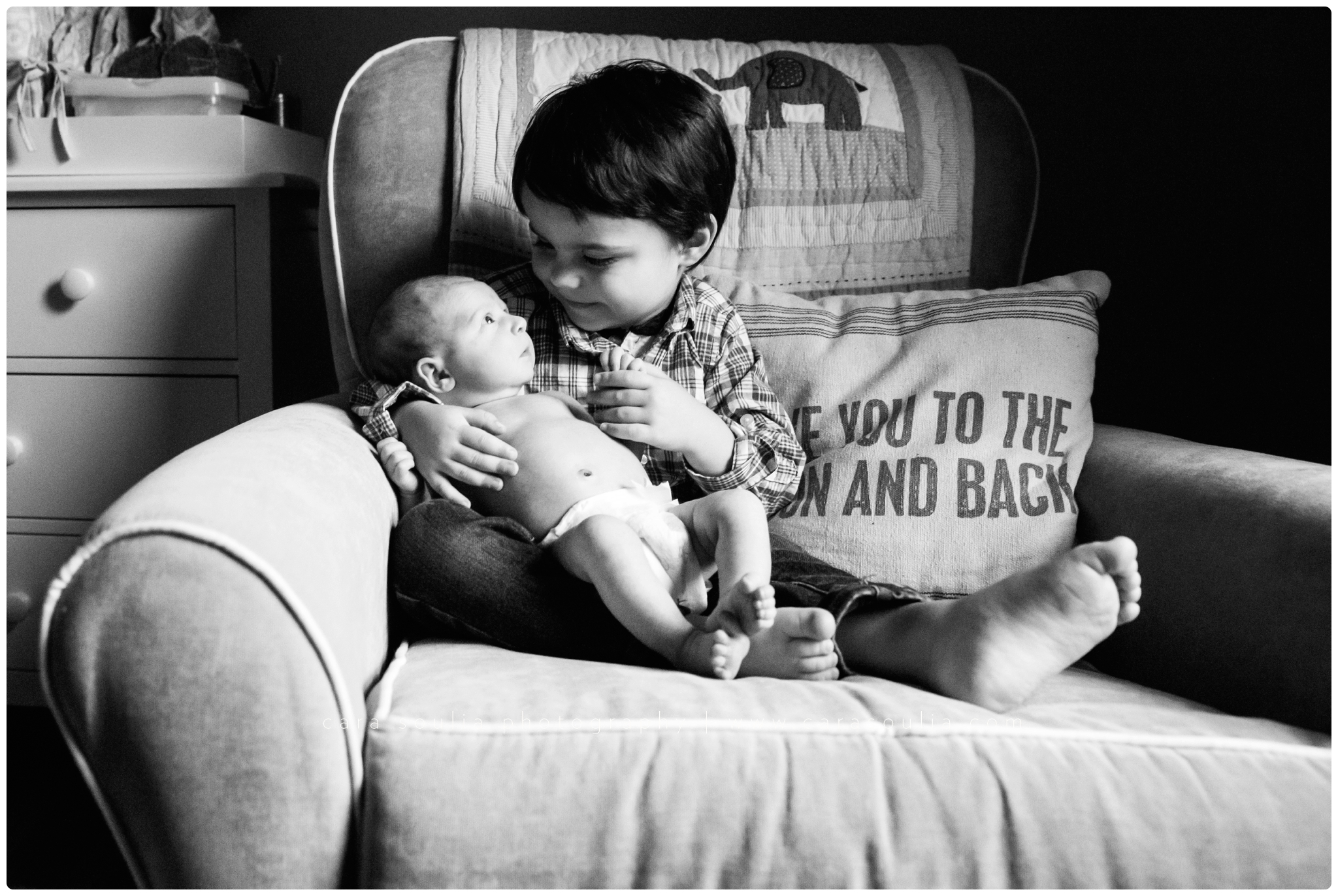 Big brother loves his new baby brother at newborn photo session in Boston
