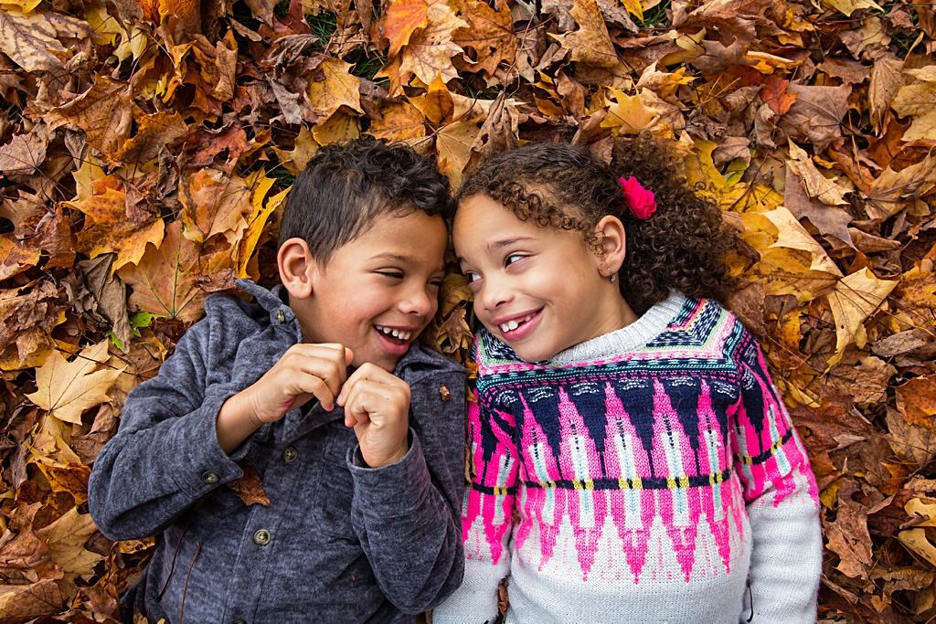 Sibling love in the leaves during a photo session in Boston